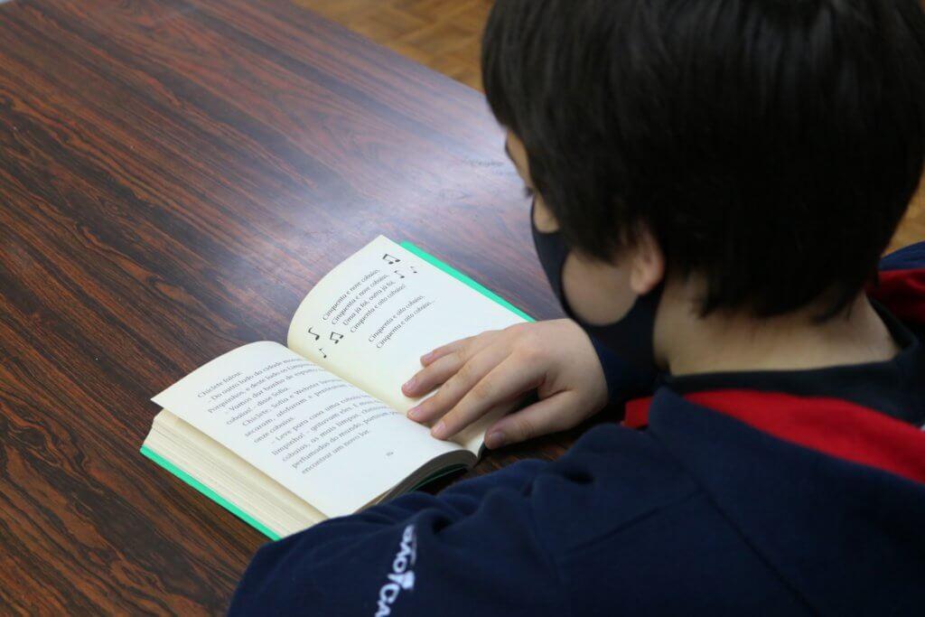 Menino uniformizado lendo livro posicionado em cima de uma mesa.